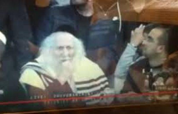 אליעזר ברלנד אומר קדיש כשהוא יושב ומדבר תוך כדי הקדיש צפו