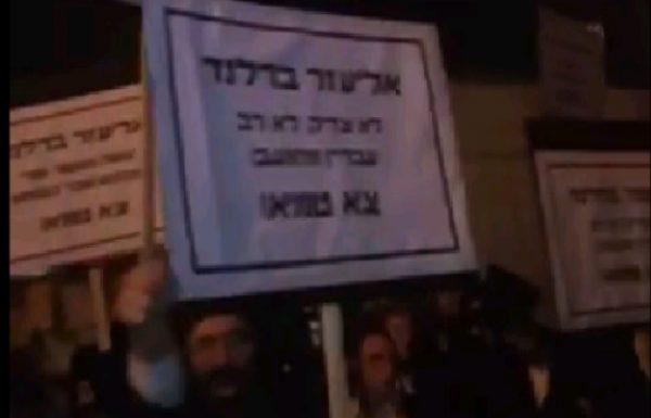 מפגינים מניפים שלטים במודיעין עילית: אליעזר ברלנד לא צדיק ולא רב עברין מתועב צא טמא צפו